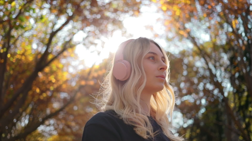 Portrait of of pretty caucasian woman in pink headphones on nature, young happy girl smiling at camera and listen music chillhop indie hip hop in autumn garden | Shutterstock HD Video #1040118704
