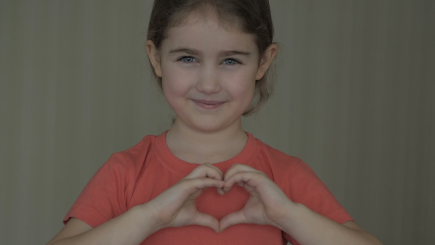 Cute little girl making a heart with her hands and smiling. Young beautiful girl smiling in love showing heart symbol and shape with hands. Romantic concept. Mothers Day.  | Shutterstock HD Video #1040137301