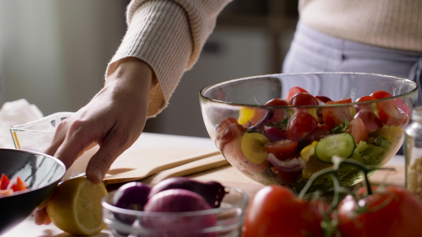Healthy eating, vegetarian food and cooking concept - woman dressing vegetable salad with squeezed lemon juice at home
