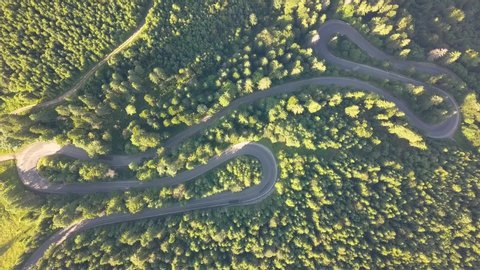 Aerial view of winding road with mowing cars and trucks in high mountain pass trough dense woods.