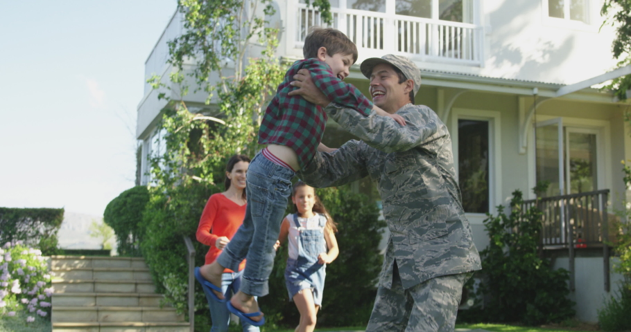 Rear view of a young adult mixed race male soldier in the garden outside his home, kneeling and picking up his young son, who runs to him holding a US flag, with his mother and sister holding hands