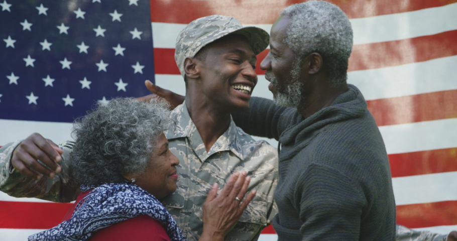 Front view close up of a happy young adult African American male soldier embracing with his parents, all of them smiling, in front of a US flag, slow motion