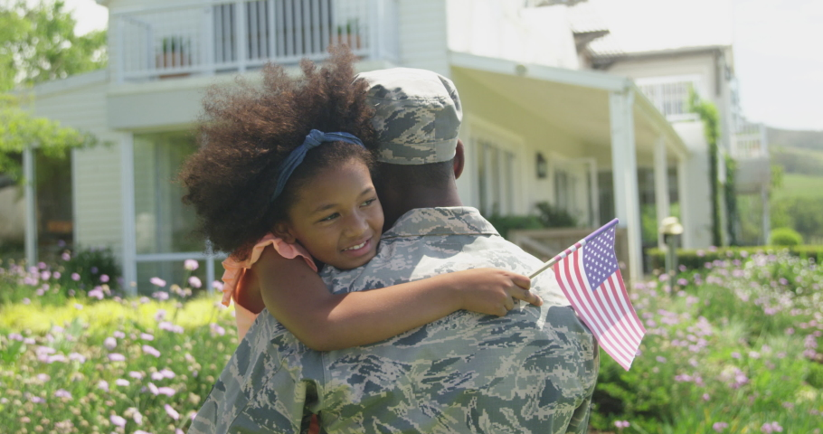 Rear view close up of a young adult African American male soldier in the garden outside his home, holding and embracing his young daughter, who is facing the camera, smiling with eyes closed