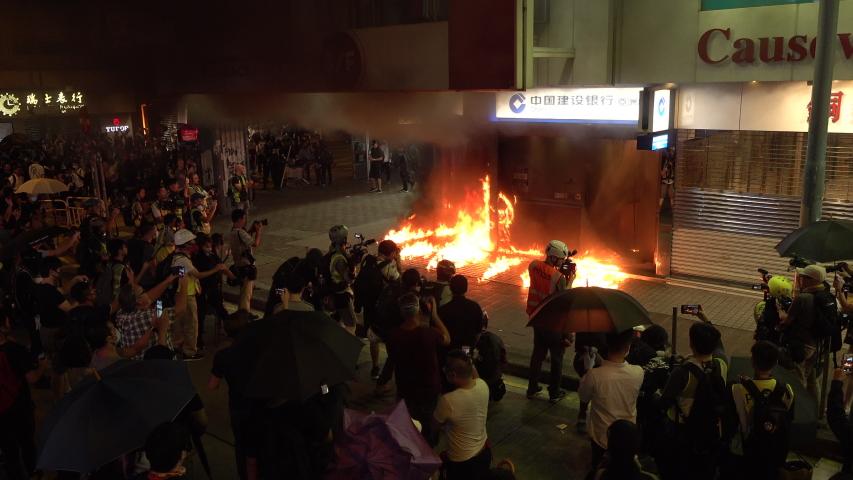 HONG KONG – 4 OCTOBER 2019: Hong Kong protests - camera crews film burning Construction Bank office after it was set on fire by angry radical demonstrators