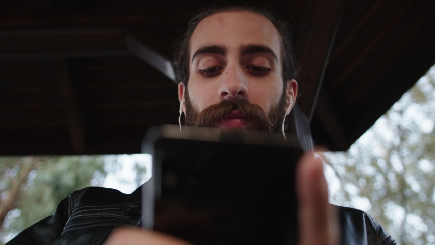 Slow motion of young handsome bearded man is texting,listening music on phone with earphones and smiling.  He is sitting in park outdoors. | Shutterstock HD Video #1040172740