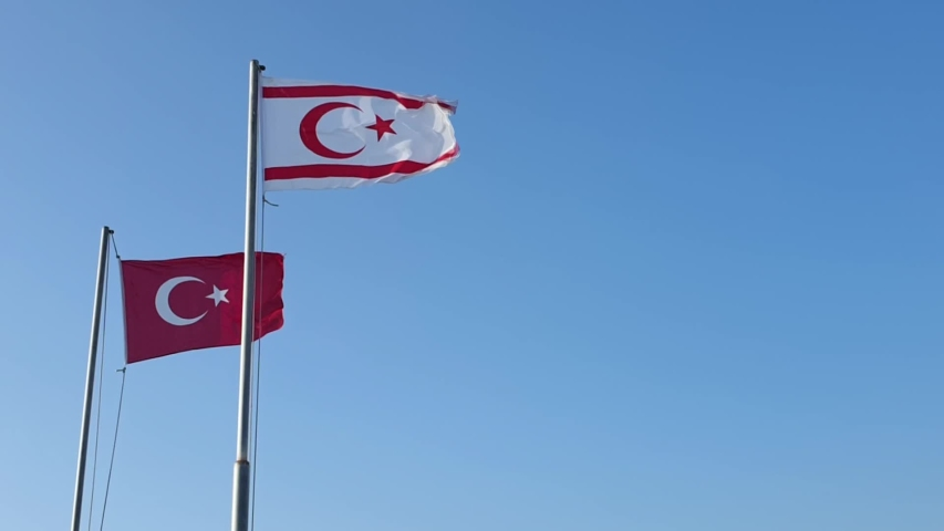 Flag of Turkey and the flag of northern Cyprus are developing in the wind against a clear blue sky, slow motion