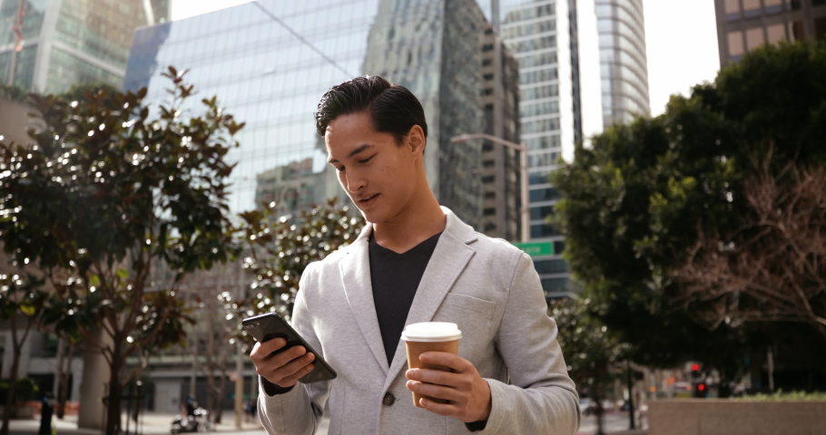Front view of a young mixed race man using a smartphone and holding takeaway coffee, standing in the city street with buildings in the background | Shutterstock HD Video #1040188316