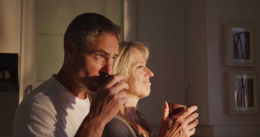 Side view close up of an adult Caucasian couple drinking cups of coffee at home, standing together in their kitchen and a woman, Social distancing and self isolation in quarantine lockdown for Covid19 | Shutterstock HD Video #1040197871