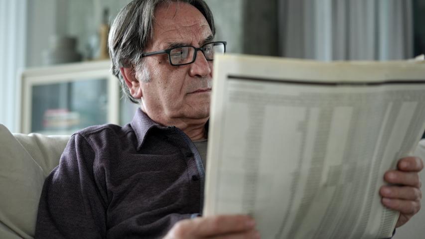 Senior man reading newspaper at home | Shutterstock HD Video #1040207888