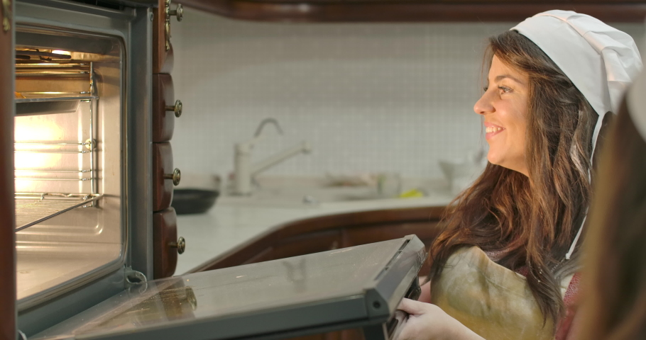 Young Caucasian mother with pleasant smile taking fresh baked buns from the oven and blowing on hot cookies. Woman cooking for her daughter standing next to her. Cinema 4k footage ProRes HQ.