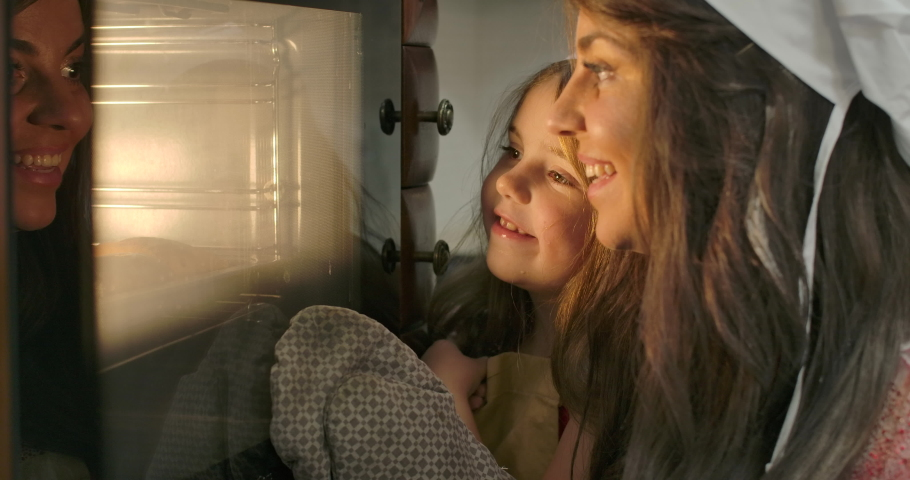Close-up faces of little Caucasian brunette girl and her mother looking into oven. Happy smiling family baking at the kitchen at home. Cinema 4k footage ProRes HQ.