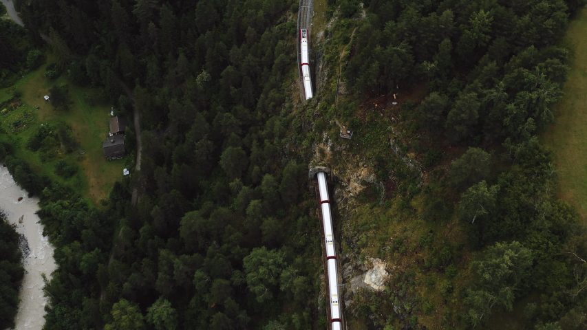 Top view, drone follows famous red Glacier Express train in epic summer Switzerland Alps, travel and tourism concept.