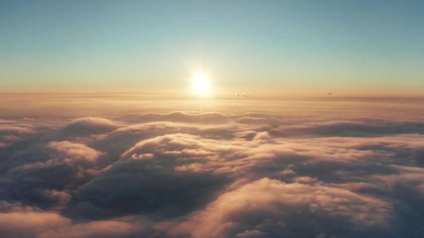 Drone flight over the clouds during sunset. Fly through the clouds. Golden hour and amazing sun rays.