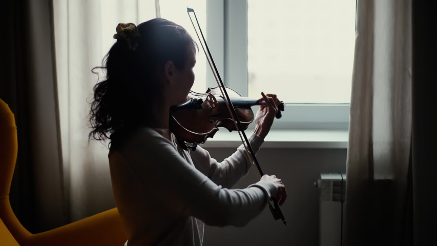 Beautiful young woman musician playing the violin by the window, sitting on soft chair in room with a modern interior. Girl is practicing playing musical instrument at home.