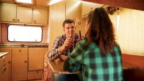 Passenger view of couple talking inside of their retro camper van. Autumn camping