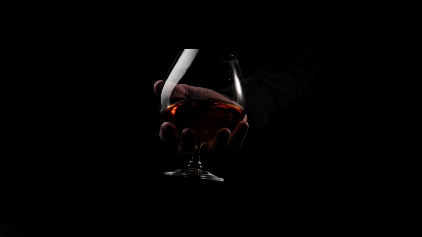 Luxury brandy. Man stir slowly golden cognac in the glass against black background. Cognac splashes in the snifter. Glass glare in the light. Brandy, cognac, snifter, binge. Slow motion.