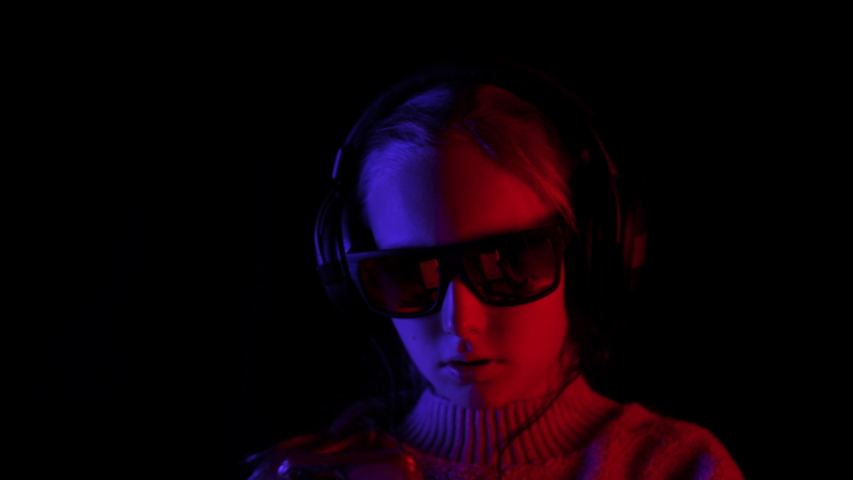 Smiling girl listening mobile music in headphones and black sunglasses in dark studio with red and blue backlight. Teenager girl browsing music in earphones on black background #1040277536