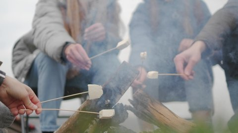 Hungry travelers are cooking marshmallow on fire and eating it from sticks during conversation around campfire,