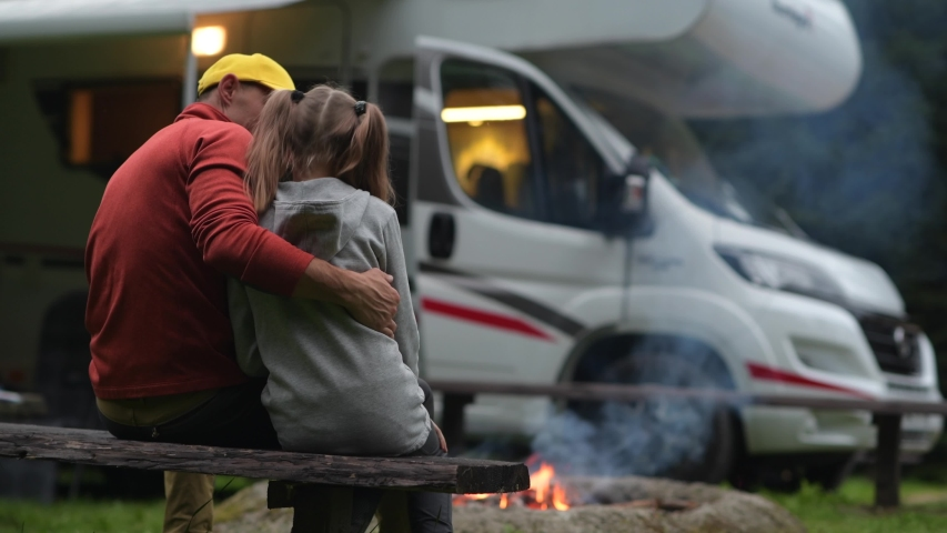 RV Campsite Family Time. Father Hugging His Daughter on Wooden Bench in Front of Campfire and Motorhome. | Shutterstock HD Video #1040290211