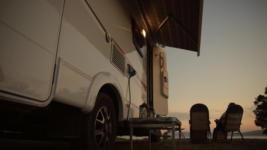 Motorhome Camping Vacation. Woman Relaxing in Front of Her Camper Van Motorhome. Royalty-Free Stock Footage #1040290271