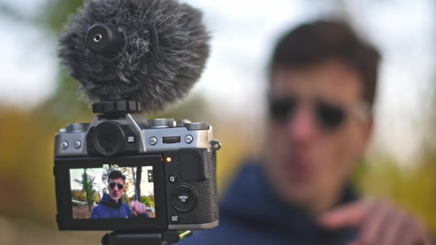 Young man vlogger speaking motivationally to the camera with an autumn park blurred backgroud | Shutterstock HD Video #1040293652