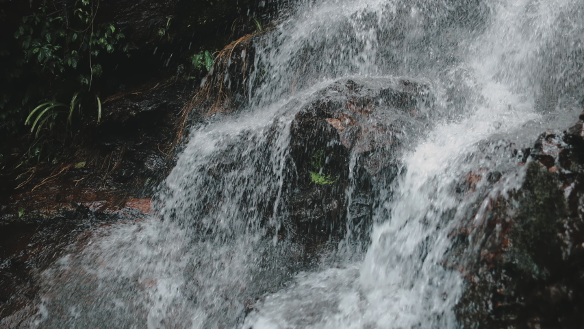 Mountain Cascade Waterfall Wild Tropical Stream. Babbling on Rocks in Rainforest. Fresh Clear Water Flowing. Tropic Lush on Stones Close up. Thailand Province Forest. Footage Shot in 4K