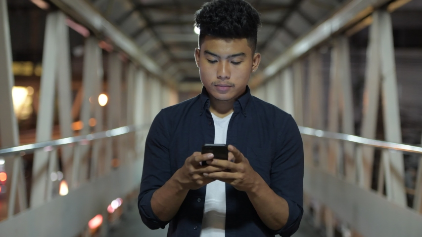 Happy young Asian man using phone on the footbridge at night | Shutterstock HD Video #1040305742