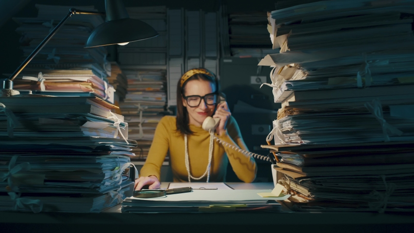 Angry stressed businesswoman sitting at office desk overloaded with paperwork, she screams at the phone