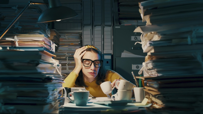 Exhausted bored woman working until late in the office, she had many cups of coffee and she is overloaded with paperwork | Shutterstock HD Video #1040314424