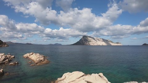 Stunning timelapse footage of the white clouds moving in the blue sky over the Sardinian sea and the island of Tavolara in the background
