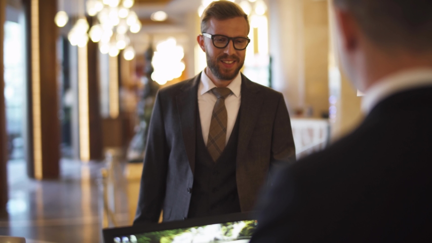 Businessman in suit carrying a suitcase man goes to reception of hotel and receives a key card from the room, business trip.
