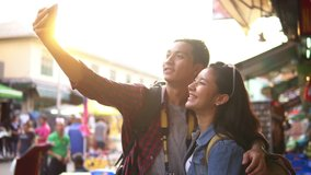 Young fun happy Asian tourist backpacker couple making video call with smartphone on Khao San Road market Bangkok Thailand during sunset in slow motion