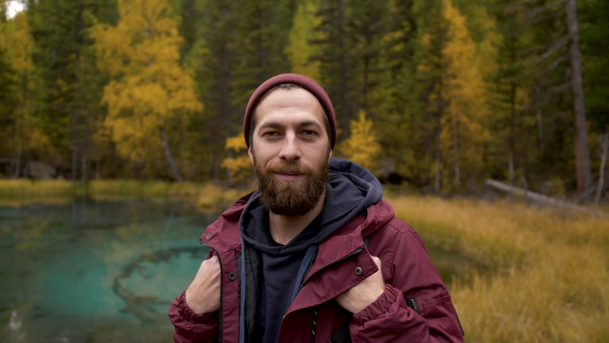 Portrait of Young Smiling Man Standing in Forest. Traveling Concept People in Nature. One 30s Person Tourist Looking at Camera On the Background of Autumn Landscape Closeup. Hiker Journey in Wildlife