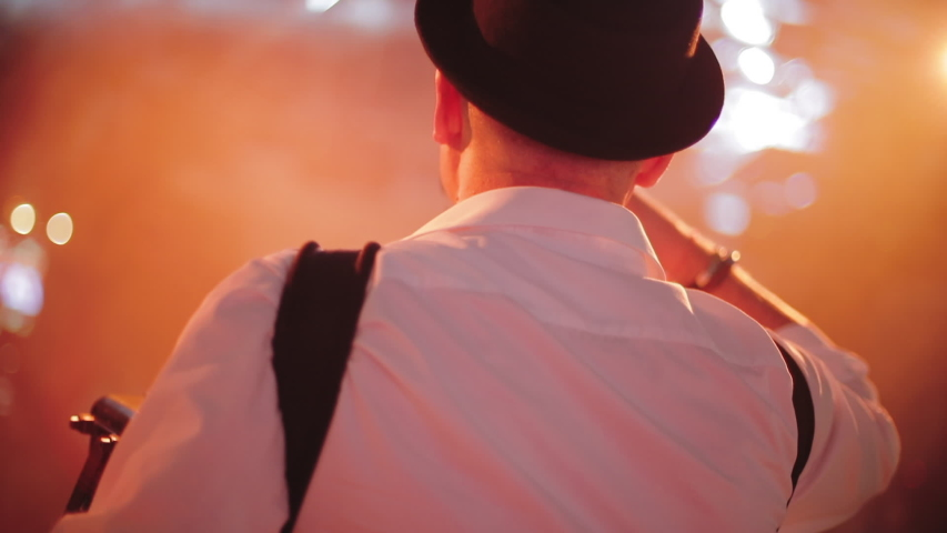 Back middle view of accordionist in hat and white shirt on stage   Shutterstock HD Video #1040339492
