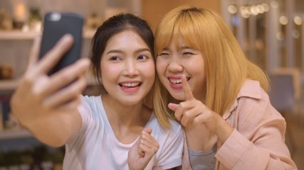 Lesbian lgbtq women influencer couple waving hand making video call at night cafe. Asian lover lady happy relax fun using technology phone record vlog video upload in social media at college campus.