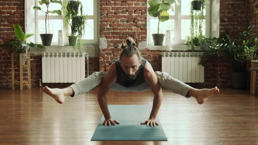 Man practice yoga pose in studio with brick wall and green plants. Fitness and healthy lifestyle concept. Bearded male making balance yoga pose in gym in slow motion. Find his harmony inside.