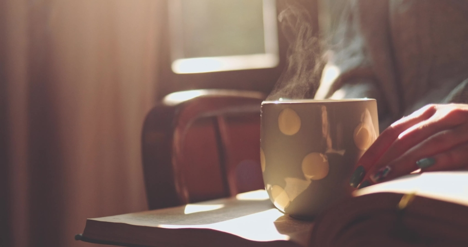 Woman Holding Steaming Cup of Tea or Coffee and Reading a Book, Enjoying Cozy Morning. SLOW MOTION, CLOSE UP. Unrecognizable Girl hands with a mug of hot drink indoors. Cinematic light. Lens Flare.