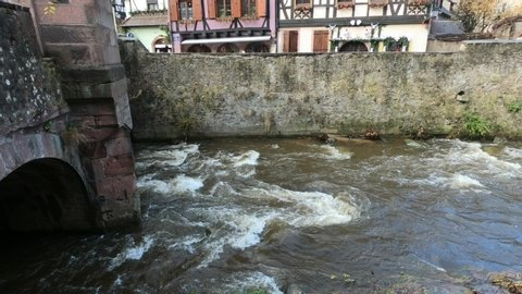 The Weiss river running between half timbered houses, Kaysersberg, Alsace, France, Europe. River with strong current flowing through the rocks.