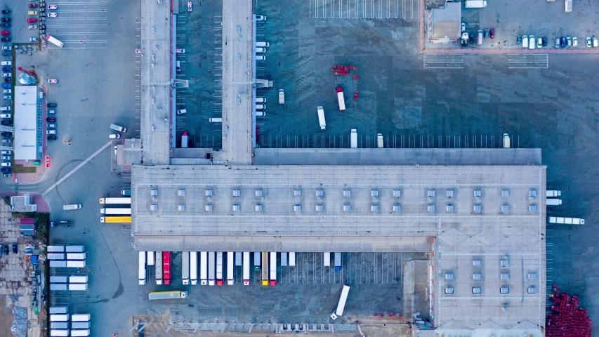 Aerial hyper lapse ( hyperlapse - time lapse), top view of the large logistics park with warehouse, loading hub with many semi-trailers trucks standing at the ramps for load/unload goods. Zoom effect | Shutterstock HD Video #1040366189