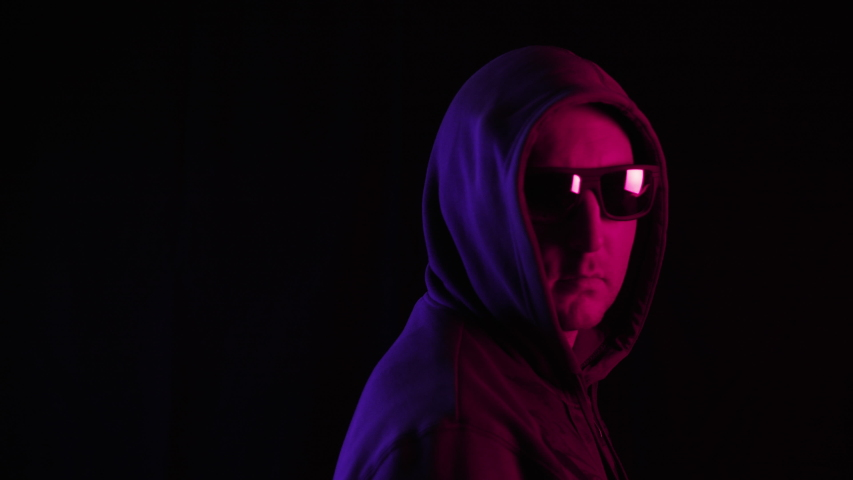 Man in hoodie and sunglasses looking at camera in darkness. Portrait of stylish serious middle aged man wearing hoodie and sunglasses, turning head and looking at camera on black background #1040373905