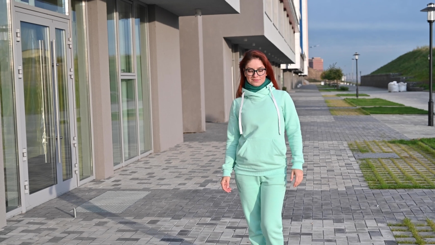 A woman in a mint warm tracksuit and scarf walks down the street and smiles. Happy red-haired girl walks in a blue sweatshirt, pants and glasses. Early sunny frosty morning.   Shutterstock HD Video #1040382200