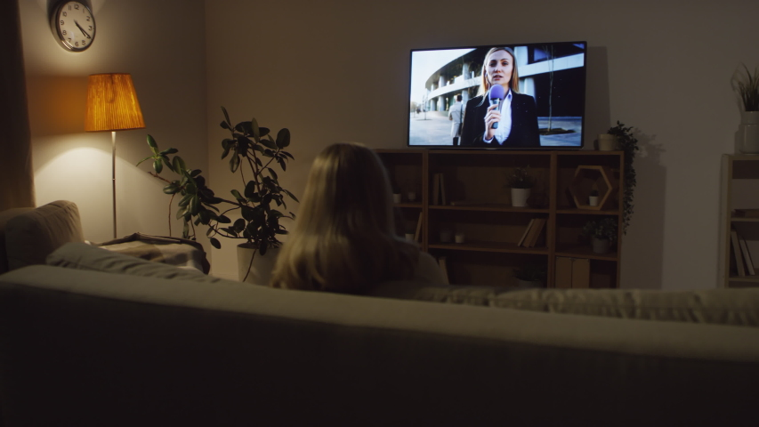 Tracking shot with rear view of woman sitting on couch in dark living room and watching evening news on TV | Shutterstock HD Video #1040385818