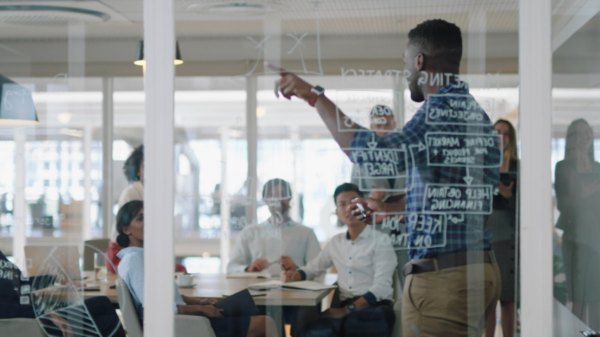 young african american businessman writing on glass whiteboard team leader training colleagues in meeting brainstorming problem solving strategy sharing ideas in office presentation seminar 4k
