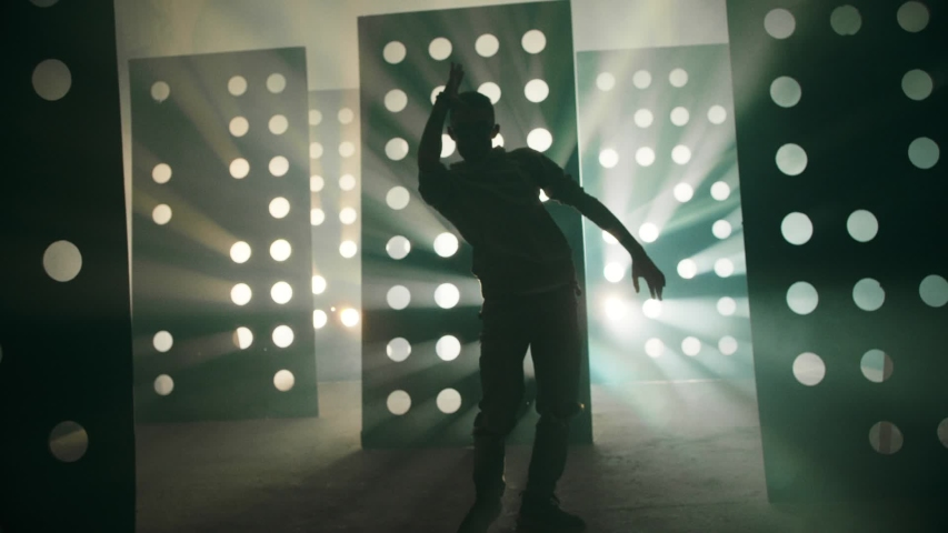 Professional Hip Hop , freestyle or swag dancer . Stylish young man dancing cyber or robot style dance near decorative walls with many circle holes and spotlight . Real decoration with round figures . | Shutterstock HD Video #1040405876