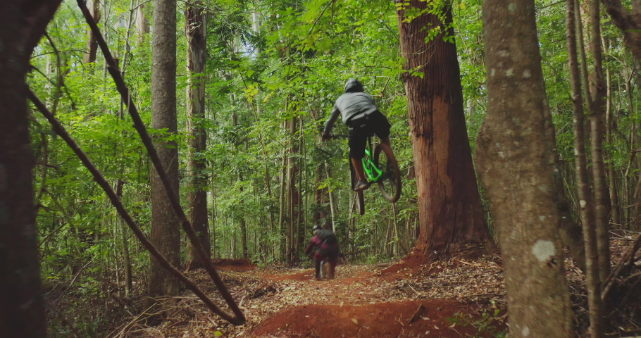 Aerial view of two professional mountain bikers going off of a jump and flying into the air going downhill on a forest trail, friends outdoors mountain biking together, summer fun activities Royalty-Free Stock Footage #1040430320