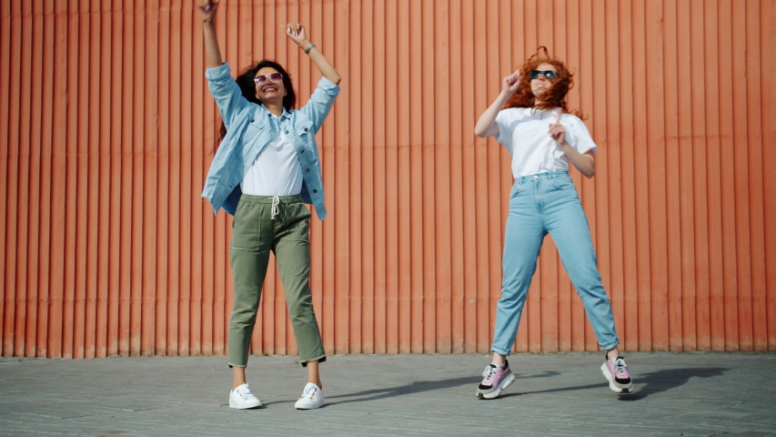 Happy girls Asian and Caucasian are dancing outdoors in city street having fun together laughing. Modern lifestyle, friendship and happiness concept. | Shutterstock HD Video #1040436260