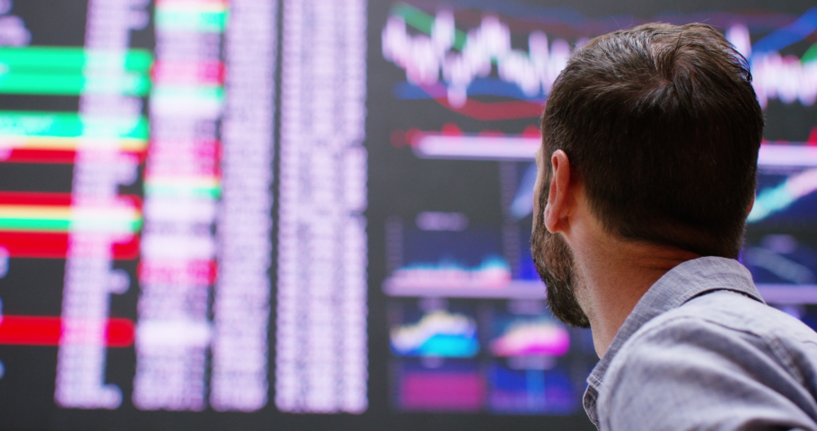 4k Happy and cheerful businessman checking stock market data at a stock exchange floor. Royalty-Free Stock Footage #1040438132