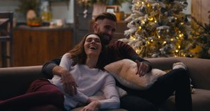 Caucasian couple sitting together on a sofa and watching TV at home during Christmas holidays, decorated apartment interior. 4K UHD RAW graded footage
