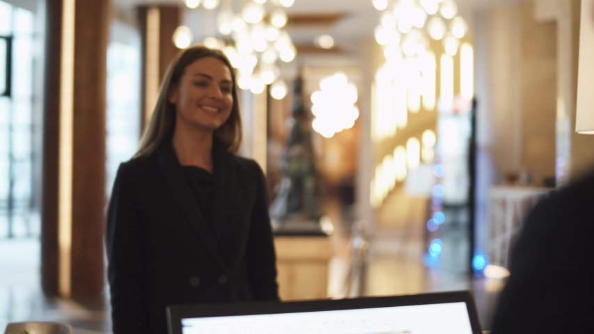 Business woman goes to reception of hotel and receives a key card from the room, woman in business trip.