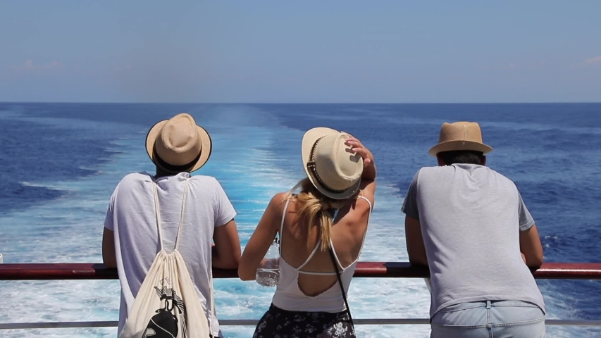 Tourists with a straw hat stand on the deck of a cruise ship and look out over the ocean while the boat is sailing.   Shutterstock HD Video #1040456330